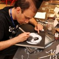 Shadows of Esteren artist Frédéric Pinson adding some personal touches to books available to Liburnicon 2014. visitors